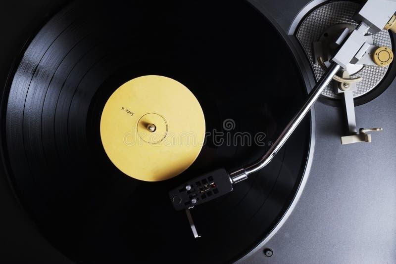 Vinylaufzeichnung mit dem gelben Aufkleber, der auf einer Drehscheibe spielt stockbilder