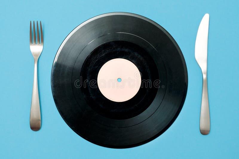 Vinylrekord med gaffeln och kniv på en blå bakgrund Bra smak i musik royaltyfria foton