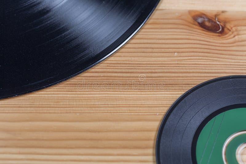 Vinylrekord och CD-SKIVA på träbakgrund arkivfoton