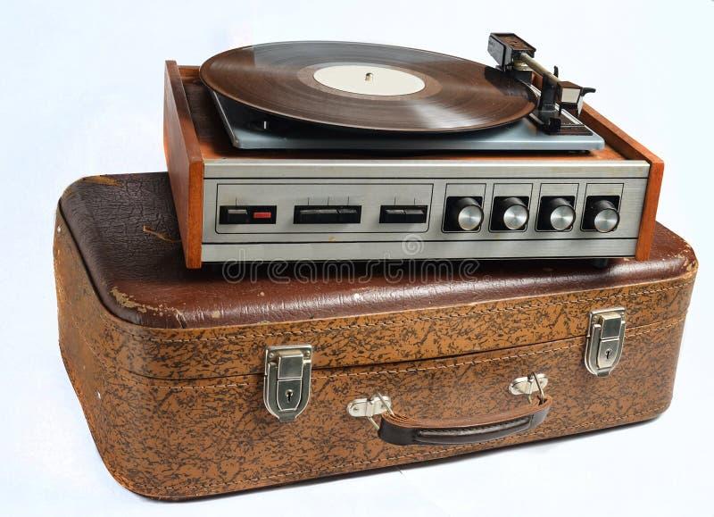 Vinylspeler op een oude die leerkoffer op een whiteVinylspeler wordt geïsoleerd op een oude geïsoleerde leerkoffer stock foto's