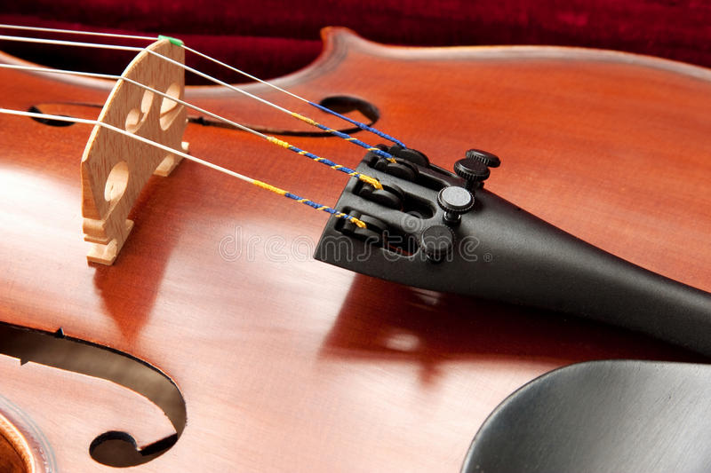 Vioin Bridge and Strings. Close up of a violin bridge, strings, tailpiece, fine tuner and f holes stock image