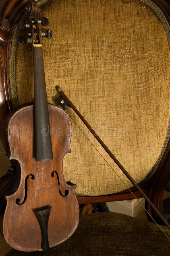 Violín, arqueamiento, y silla antiguos imagen de archivo