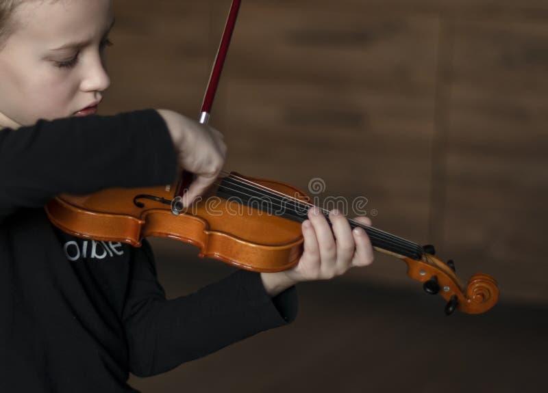 Violín del control de la manija Violín que lleva del niño pequeño Muchacho joven que toca el violín, jugador talentoso del violín fotos de archivo libres de regalías
