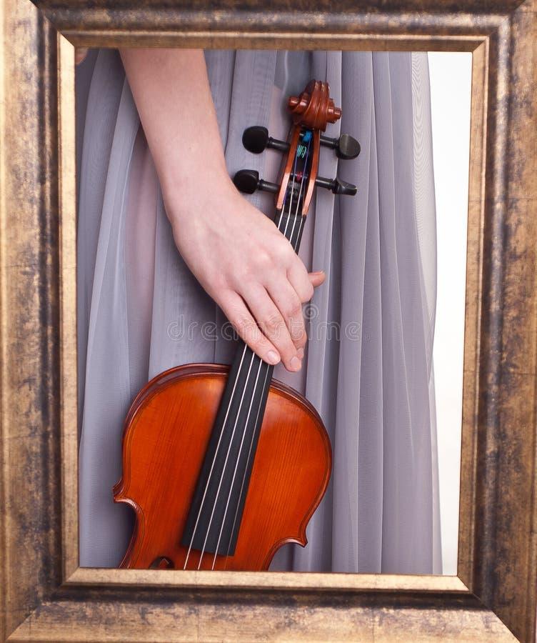 Violín a disposición de una mujer joven vista a través de un marco foto de archivo