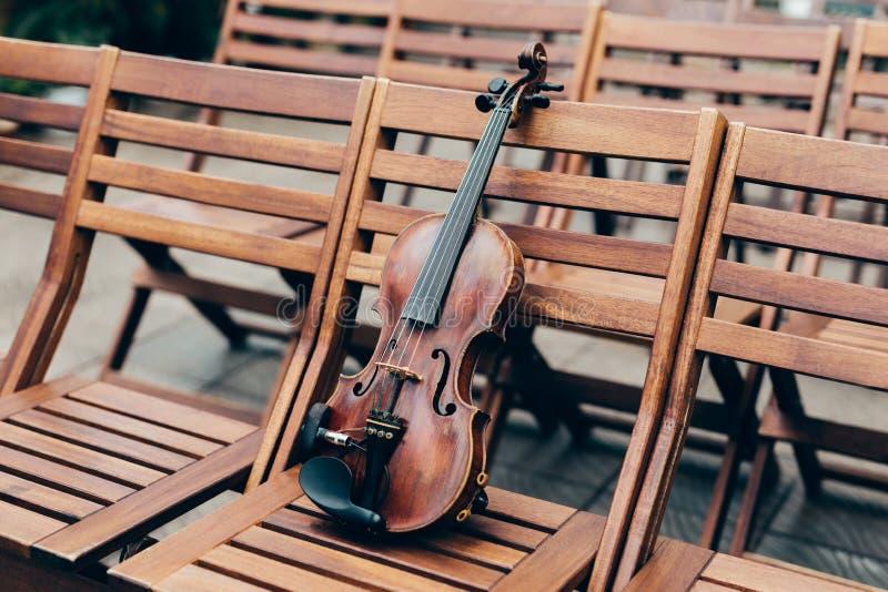 Violín en silla de madera en jardín Preparación para el concierto o el funcionamiento Instrumento musical de la secuencia en aire fotografía de archivo libre de regalías