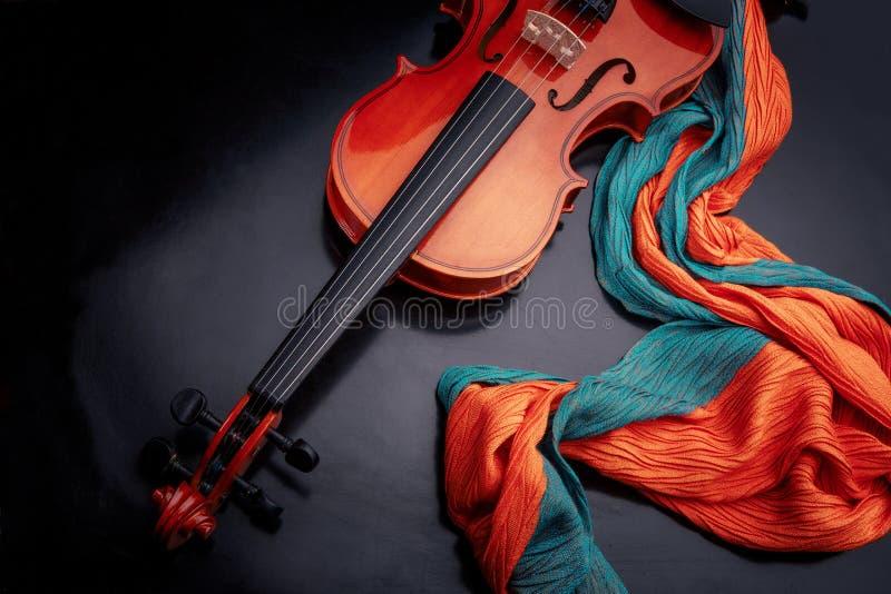 violín en una tabla negra con una bufanda del color imagen de archivo
