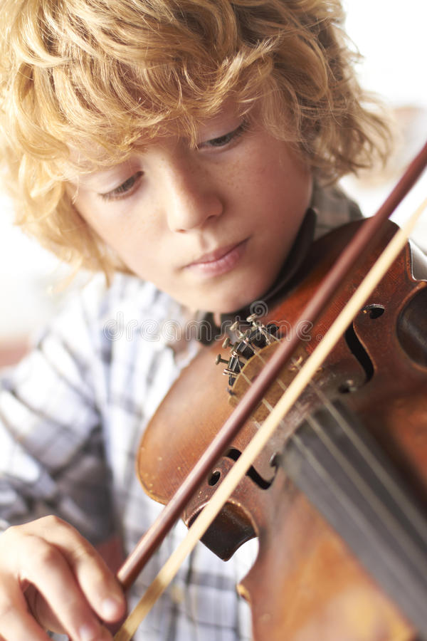 Violín practicante del muchacho en el país imagen de archivo