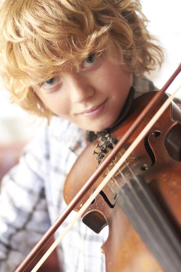 Violín practicante del muchacho en el país foto de archivo