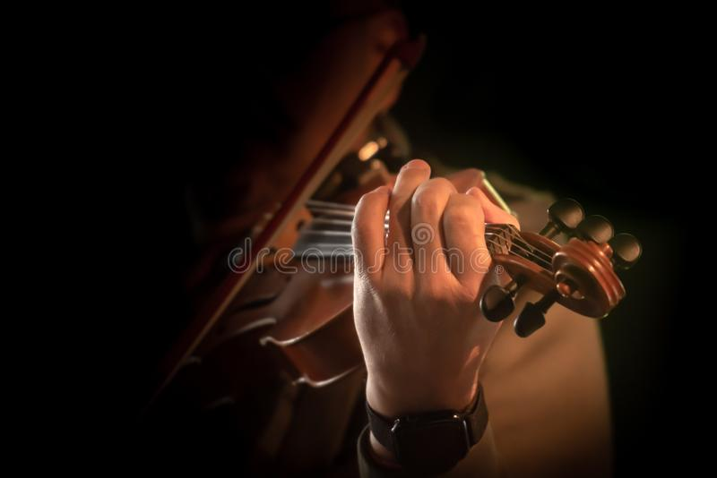 Violín que juega al músico en primer delante del fondo negro fotos de archivo