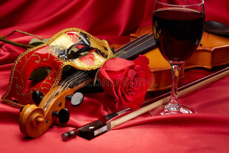 Violín, rosa del rojo y máscara del teatro fotografía de archivo