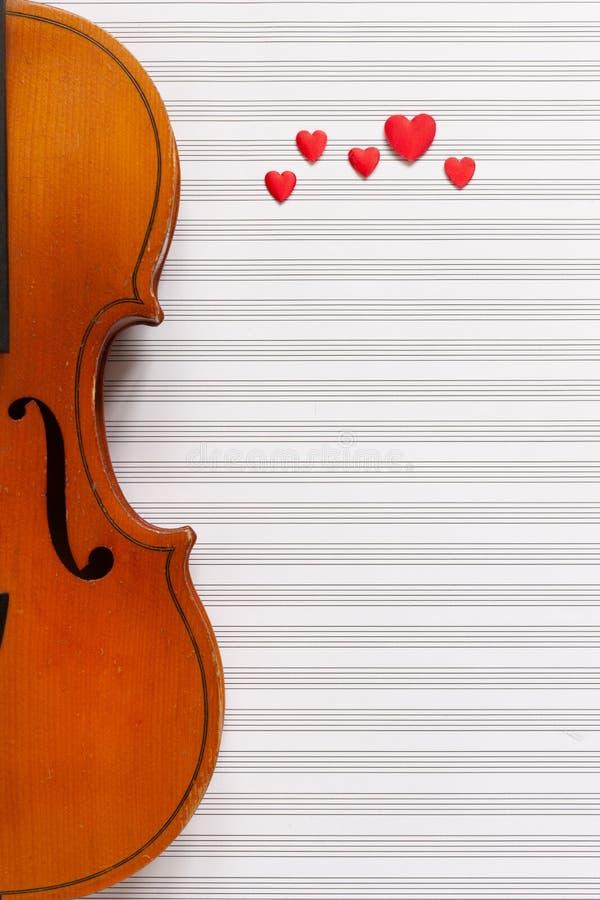 Violín viejo y estatuillas rojas del corazón La visión superior, cerca para arriba, pone completamente en el fondo blanco de pape foto de archivo