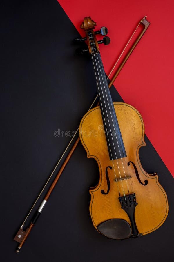 Violín y arco en un fondo rojo y negro foto de archivo libre de regalías