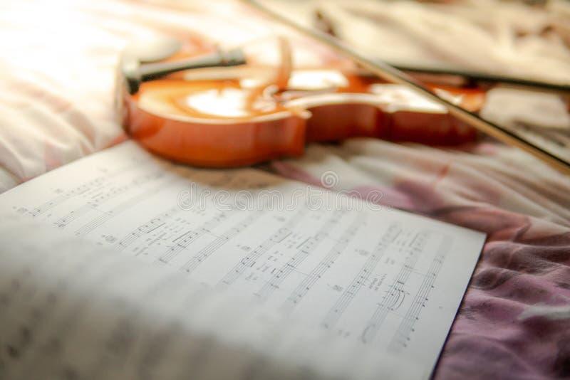 Violín y la hoja de la nota de la música sobre la cama imagen de archivo