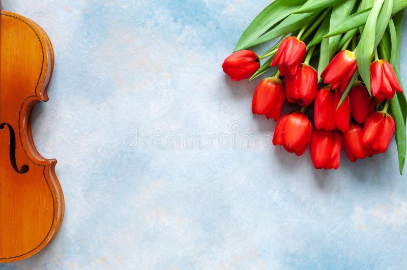 Violín y ramo viejos de tulipanes rojos Día de San Valentín, el 8 de marzo concepto Visión superior, primer en fondo concreto del fotos de archivo libres de regalías