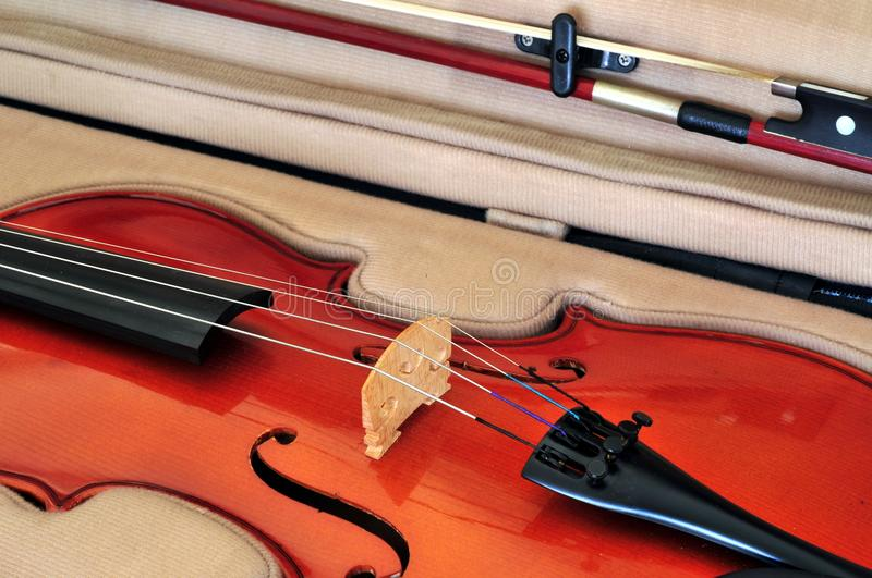 Viola and bow in case. Viola in its case showing f-holes, bridge, fingerboard, chinrest, tailpiece with fine tuners and bow royalty free stock photography