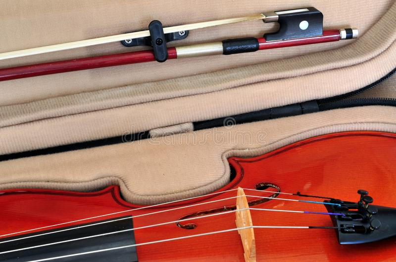 Viola and bow in case. Viola in its case showing f-holes, bridge, fingerboard, tailpiece with fine tuners and bow stock photography