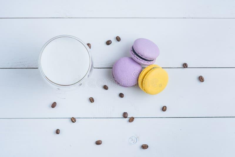 Viola deliziosa dolce e macarons e tazza gialla di latte o americano e chicchi di caffè sparsi su di legno bianco fotografia stock libera da diritti