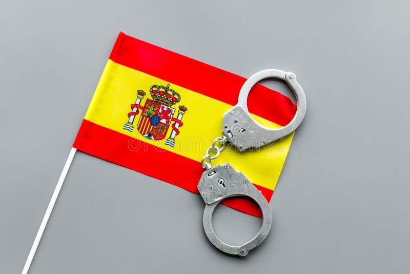 Violación de la ley, ley-rompiendo concepto Esposas del metal en bandera española en la opinión superior del fondo gris fotos de archivo
