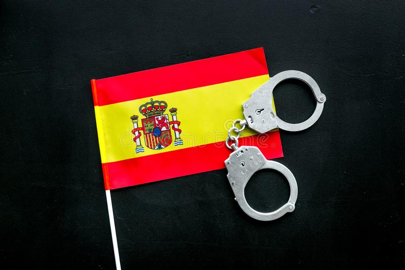 Violación de la ley, ley-rompiendo concepto Esposas del metal en bandera española en la opinión superior del fondo negro foto de archivo libre de regalías
