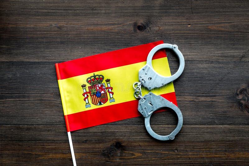 Violación de la ley, ley-rompiendo concepto Esposas del metal en bandera española en la opinión de top de madera oscura del fondo fotos de archivo