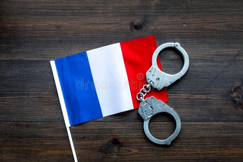 Violation de loi, loi-cassant le concept Menottes en métal sur le drapeau français sur la vue supérieure de fond en bois images libres de droits