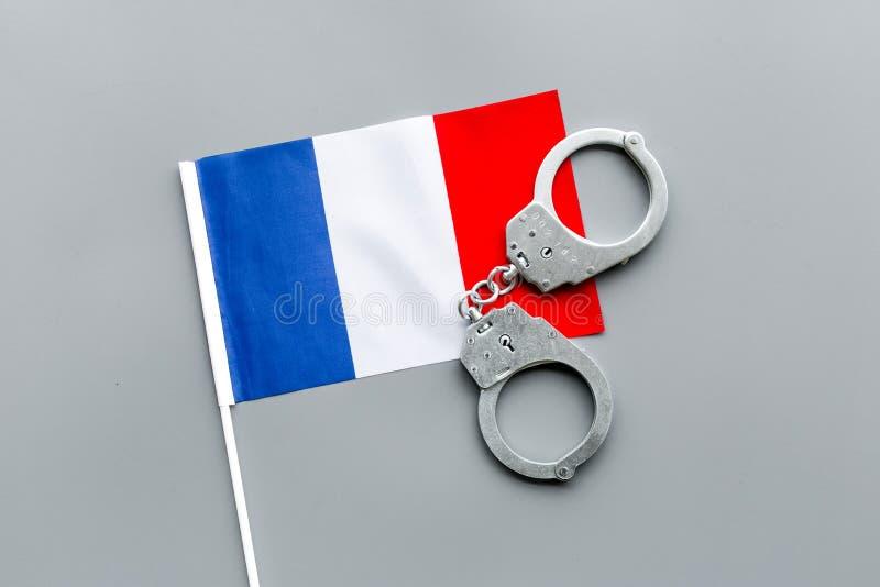 Violation de loi, loi-cassant le concept Menottes en métal sur le drapeau français sur la vue supérieure de fond gris photographie stock libre de droits