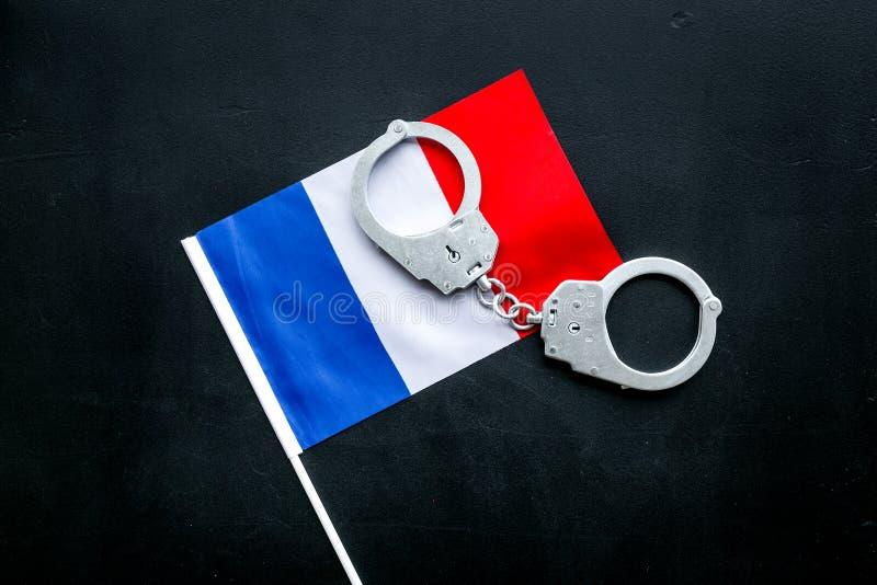 Violation de loi, loi-cassant le concept Menottes en métal sur le drapeau français sur la vue supérieure de fond noir images libres de droits