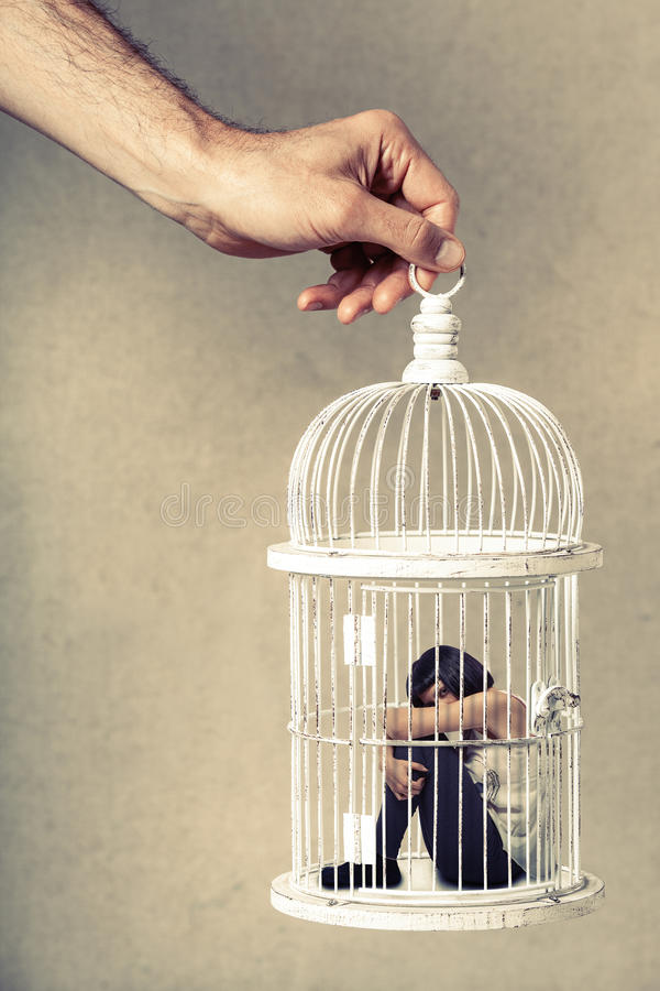 Violence against women. Woman in cage. Deprivation of liberty. Young woman locked in a cage. Young girl crouched position. A male hand holding the cage from stock photos