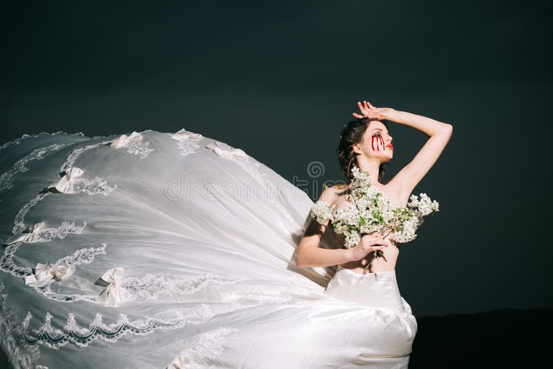 Violence and cruelty. bloody tears on face of halloween woman in wedding dress. violence and cruelty concept. Which royalty free stock photo