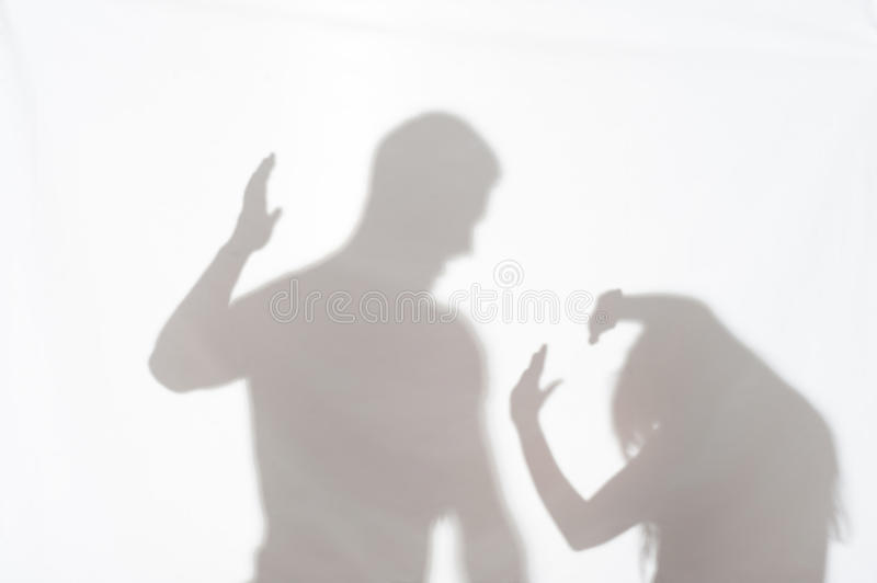 Violence of man against woman. Silhouette of men striking the women who cannot to protect herself stock photography