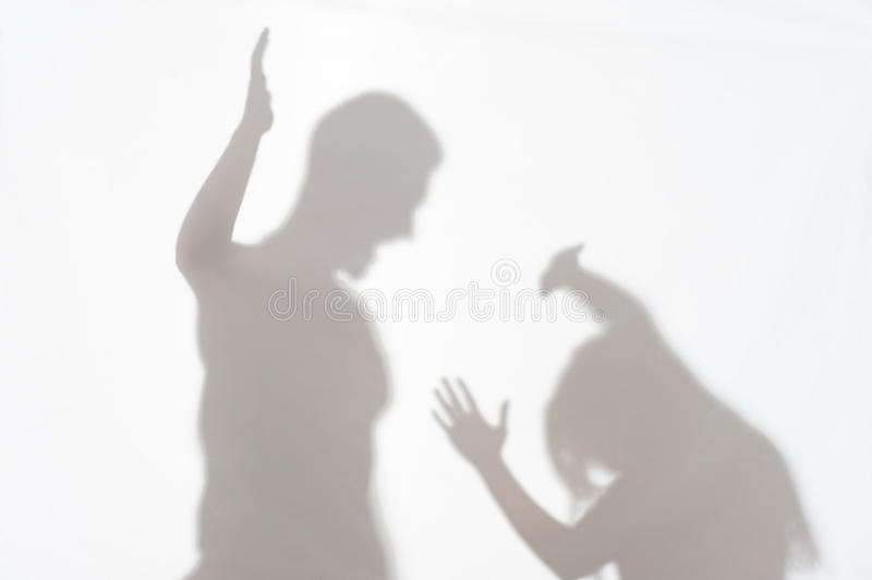 Violence of man against woman. Silhouette of men striking the women who cannot to protect herself royalty free stock photo