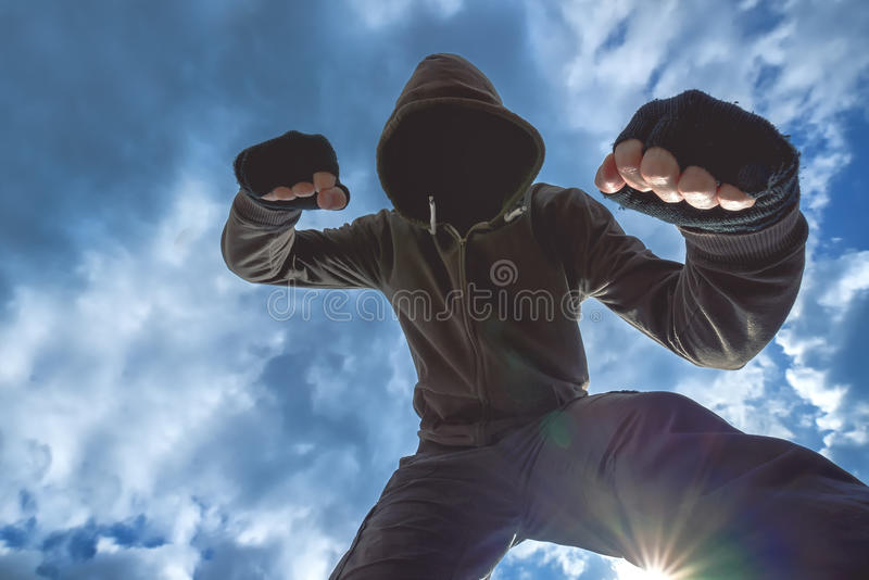 Violent attack, unrecognizable male criminal kicking and punching victim royalty free stock photos