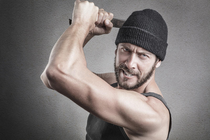 Violent man using a spanner or wrench as a weapon. And looking at camera, close up head and shoulders stock photography