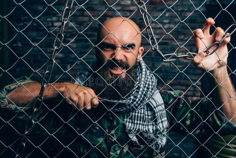 Violent terrorist with knife against metal grid. Bearded violent terrorist with knife against metal grid, male mojahed. Terrorism and terror, soldier in khaki royalty free stock photos