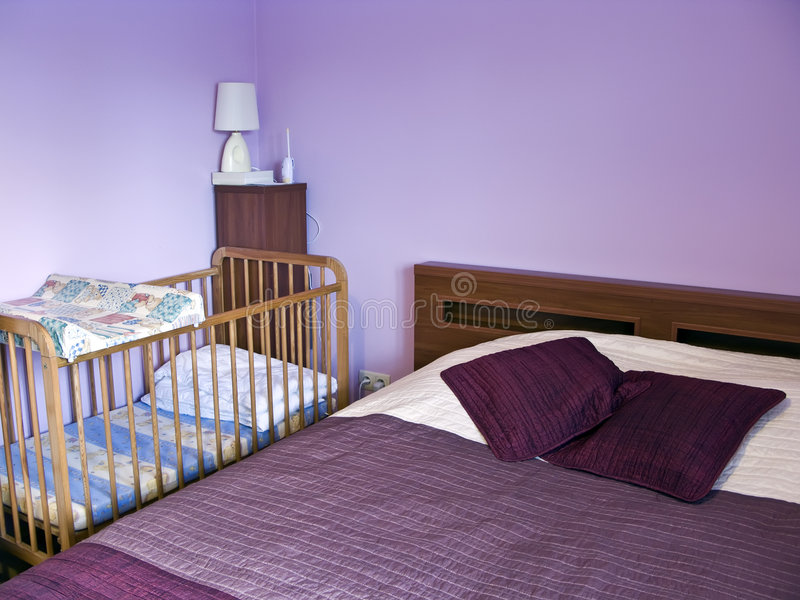 Violet bedroom. A bedroom with walls painted in violet, the bedcover is also violet. A childs bed with a small cupboard at the side stock photo