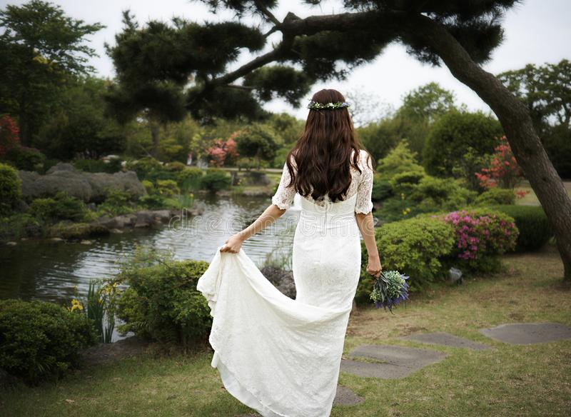 Violet bouquet held tightly in hands of a woman in white dress in a pond with pine tree in Camellia Hill of Jeju Island royalty free stock images