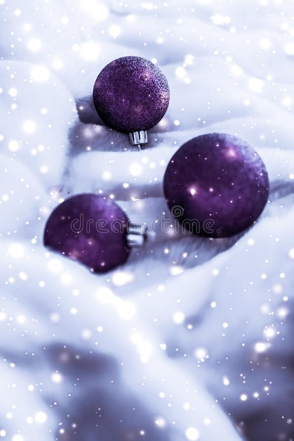 Violet Christmas baubles on fluffy fur with snow glitter, luxury winter holiday design background. Gift decor, New Years Eve and happy celebration concept stock photography