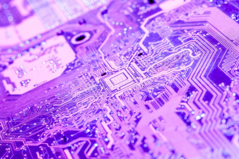 A violet circuit board close up. Close up of chips on a violet computer circuit board stock photography