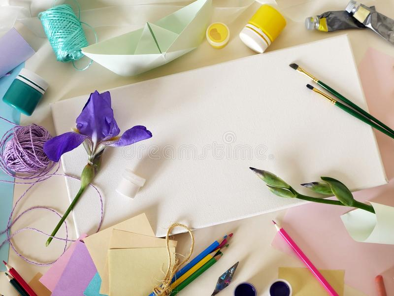 Violet flower adorns a white canvas, materials for drawing and creativity royalty free stock photography
