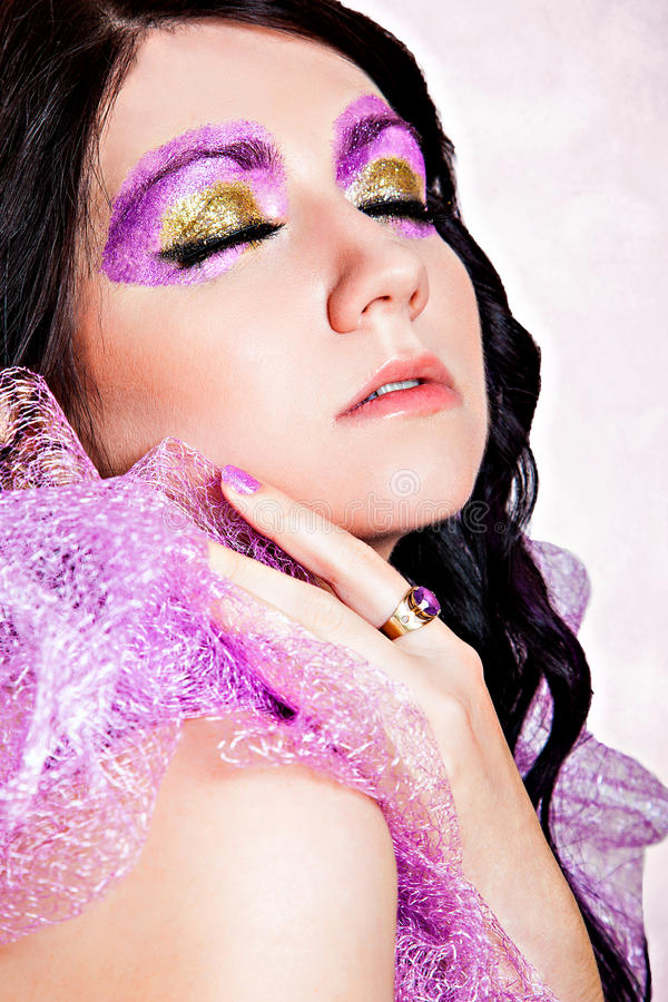 Violet and gold glitter eye-make-up. Sensual beautiful girl with violet shiny glitter make-up royalty free stock photos