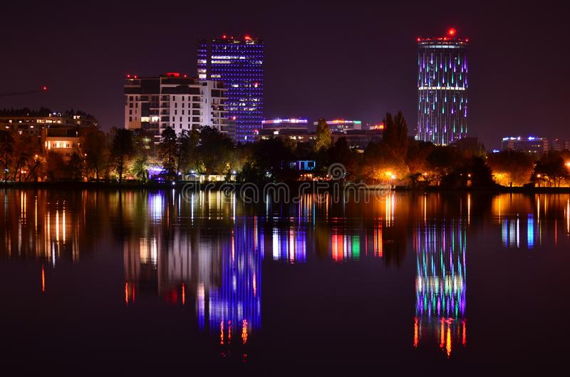 Bucharest night scene with colorful reflection. Night scene with modern building covered in violet and blue lights reflected in lake water surface. Bucharest