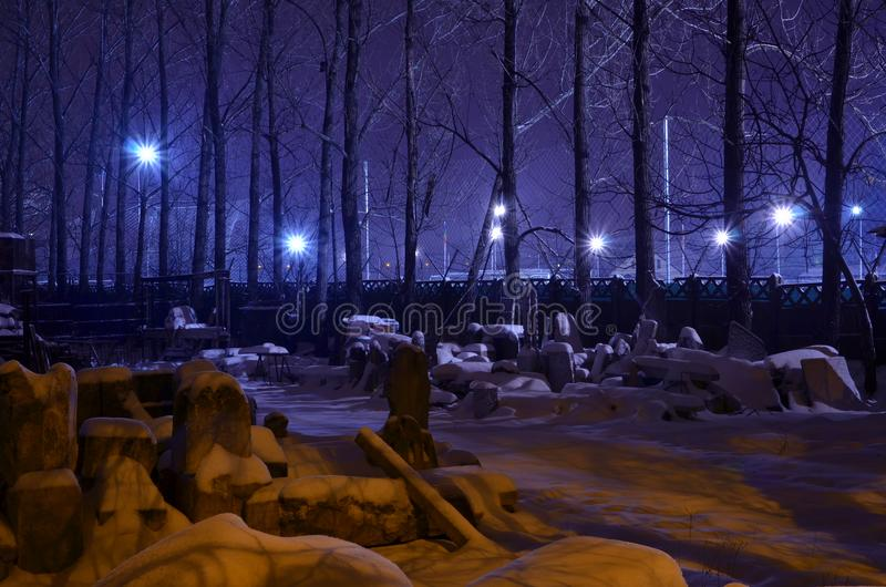 Fantasy night winter scene in purple color. Night winter scene in the city with trees, old abandoned sculptures covered by snow and fluorescent light poles
