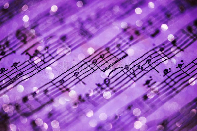 Violet music notes. Music notes sheet in violet tonality and blurred lights background
