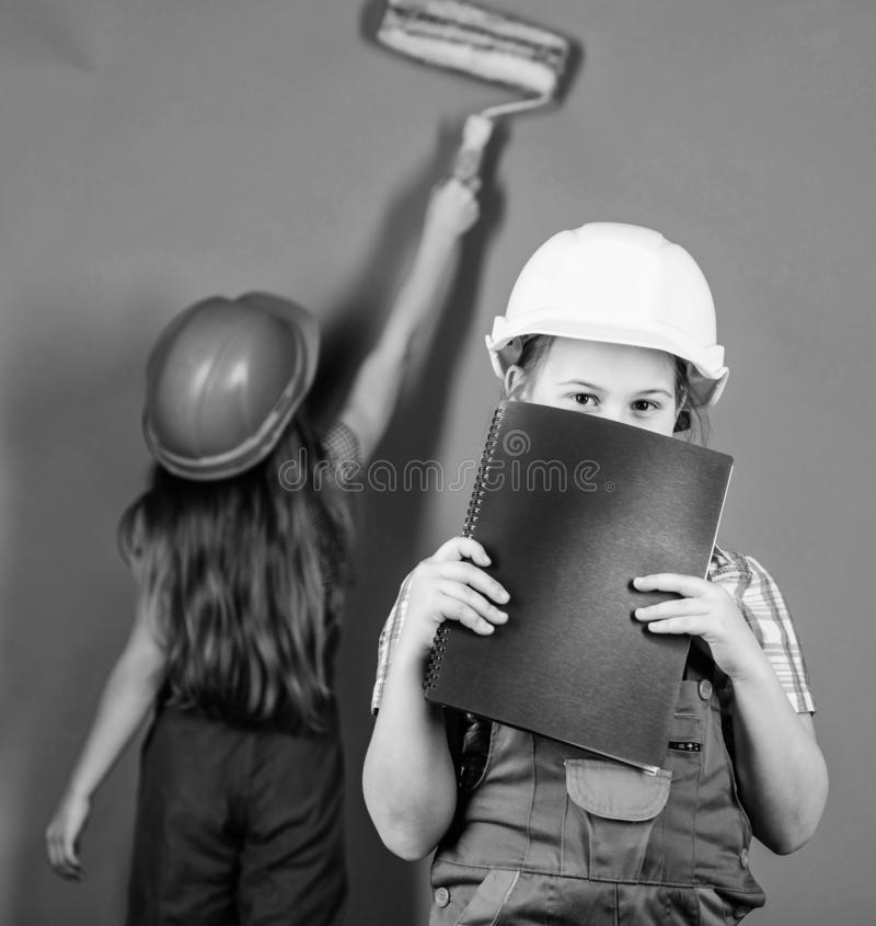 Violet is my favorite color. Children sisters renovation their room. Control renovation process. Kids happy renovating royalty free stock images