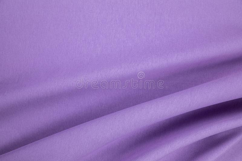 Violet natural linen fabric with a drapery folds. Close up stock photo