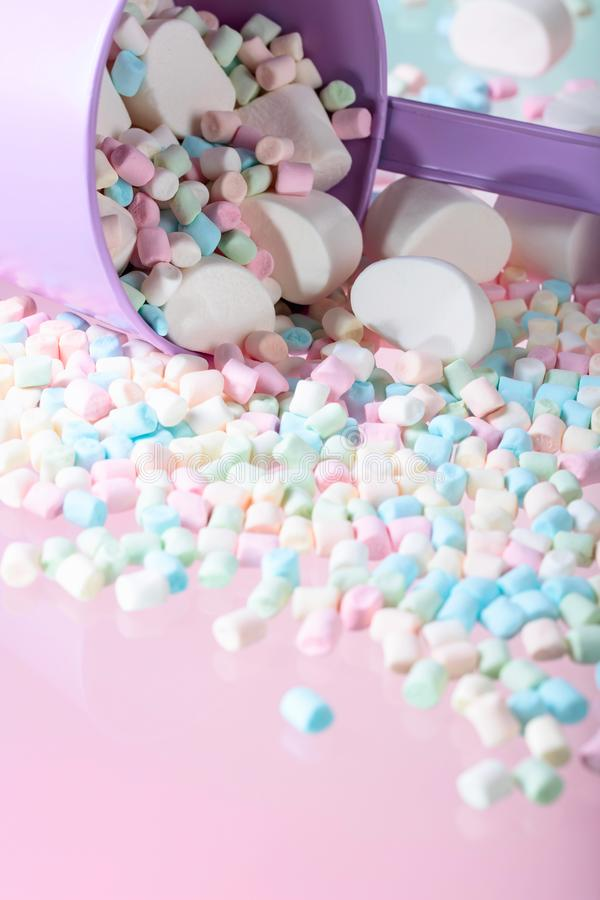 Violet pail with various marshmallows. On a pink background. Copy space royalty free stock photo
