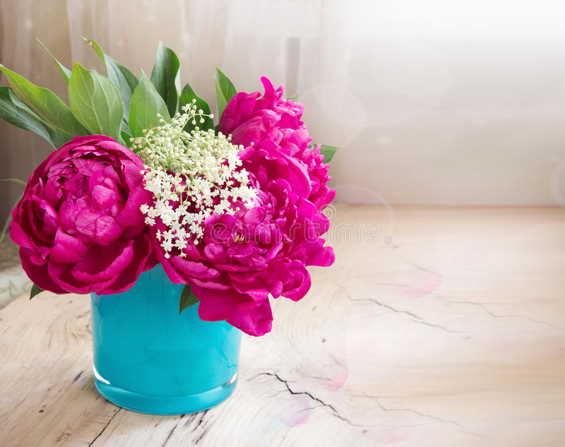 Violet peony flowers in blue vase on wooden table closeup royalty free stock photography
