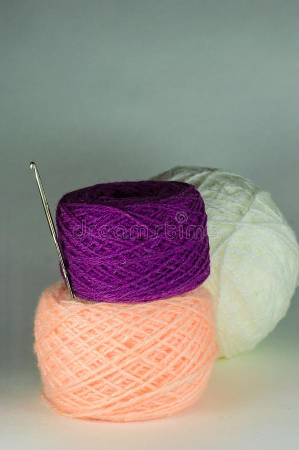 Violet and pink balls of yarn and a crochet hook. stock photography