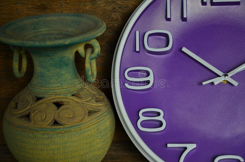 Violet clock and old jar close up stock photography