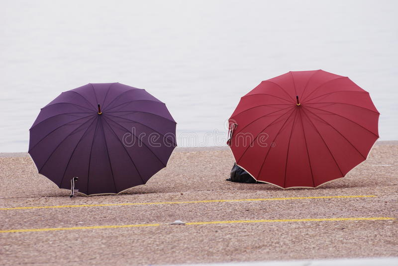 Violet and red umbrellas in Thessaloniki. On the seafront of Thessaloniki view over two open umbrellas on the floor stock image